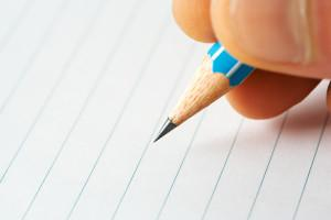 Close up of pencil tip hovering above paper