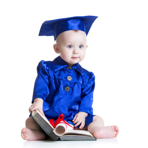 Blue eyed baby in graduation outfit with diploma