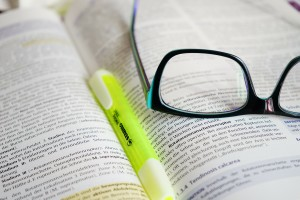 Close up of a highlighter and glasses on an open book