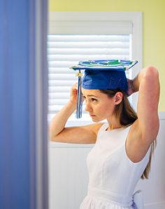 Girl in bathroom putting on her graduation cap